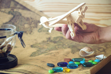 Hand holds wooden toy plane on a world map with colored stones and shells from the sea in a retro style