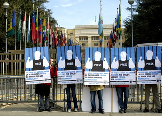 """Delegates of """"Reporters Without Borders"""" stand with posters showing the silhouettes of imprisoned jo.."""