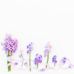 Bouquet of blue hyacinth flowers and shabby tapes on white background. Flat lay, top view. Valentine's background
