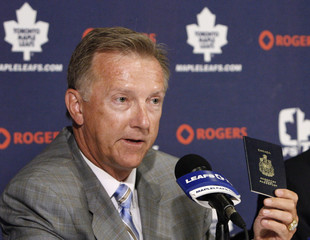 Toronto Maple Leafs new head coach Ron Wilson holds his Canadian passport during a news conference in Toronto