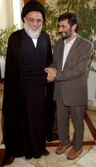 Iranian Judiciary chief Ayatollah Shahroudi shakes hands with Iran's President-elect Ahmadinejad in Tehran.
