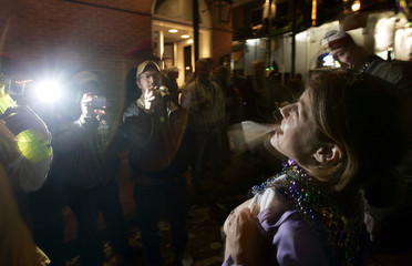 A woman lifts her shirt as revelers snap photographs in the French quarter of New Orleans