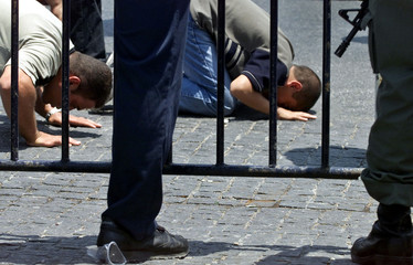 Armed Israeli police watch over Palestinians, who were denied entry to the Al-Aqsa Mosque, pray in t..