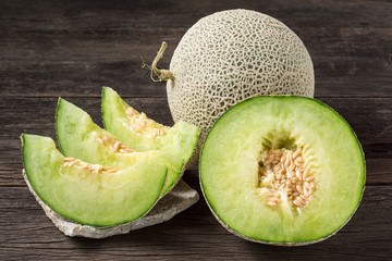 ripe and fresh melon with sliced and half on old wooden table