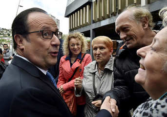 French President Francois Hollande shakes hands with residents as he visits polling stations during the second round of the 2017 French presidential election, in Tulle