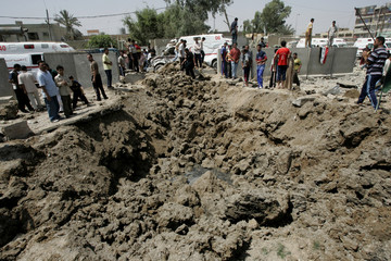 Residents look at a crater at the al-Sadr hospital compound after rocket attack in Baghdad's Sadr City