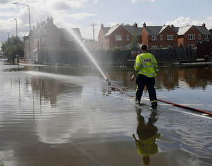 A Firefighter approaches a hose pumping out flood waters in Tewkesbury