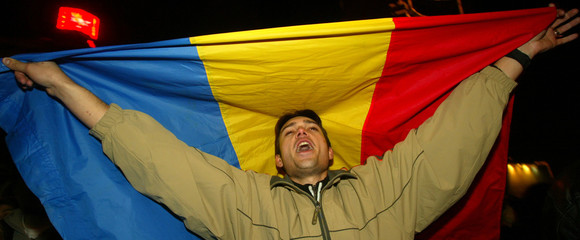 A supporter of Bucharest's popular mayor Traian Basescu celebrates with the Romanian flag in ...