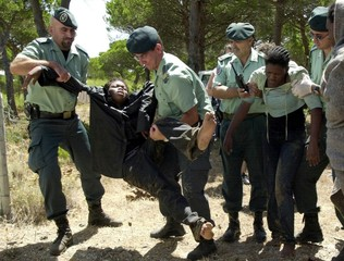 Spanish Civil Guards help to carry several illegal immigrants with symptoms of hypothermia found nea..
