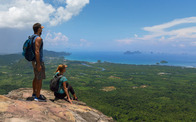 Man and woman standing on cliff's edge and looking into a Krabi wide valley,sky and clouds,Thailand