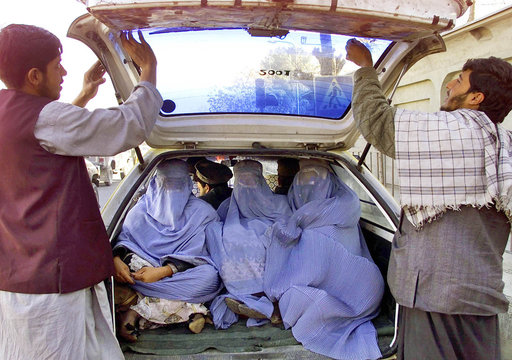 AFGHAN MEN REMOVE TINTED FILM FROM A CAR WINDOW IN KABUL.