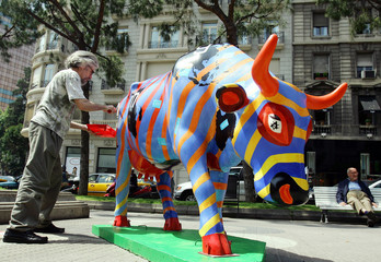 Spanish artist Jordi Traperho paints his cow sculpture part of the Cow Parade art festival in central ...