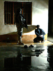 US soldier from the 1st Infantry Division guards Iraqi man detained during night raid in Baquba.