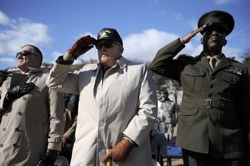 Veterans salute during the national anthem in honor the 64th anniversary of the raising of the US flag on the island of Iwo Jima during World War II, during a ceremony at the Marine Corps War Memorial in Arlington, Virginia