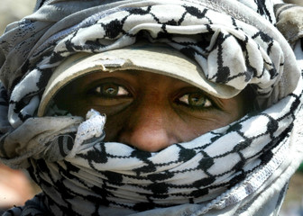 PALESTINIAN BOY ALI COVERS HIS HEAD WITH A KEFFIYA AS HE SEARCHESTHROUGH RUBBISH AT A DUMP NEAR THE ...