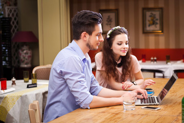 Young couple working on laptop sitting in the kitchen