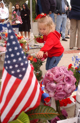 YOUNG GIRL AT FLOWERS LEFT IN MEMORY OF RONALD REAGAN.
