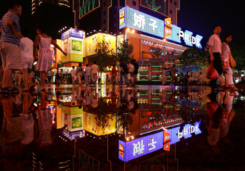 SHOPPERS WALK AT A SHOPPING DISTRICT AFTER RAIN IN CHINA'S CHENGDU.