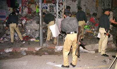 PAKISTANI POLICE OFFICIALS REMOVE THE DEBRIS FROM THE SITE OF THE BOMB BLAST IN RAWALPINDI.