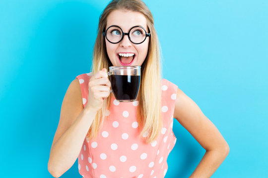 Happy young woman drinking coffee