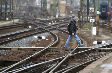 A man crosses railway tracks during an indefinite strike by railway workers at the Eastern railway station in Budapest