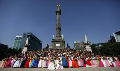 "Girls pose in front of the El Angel statue during their ""Quinceaneras"" a coming of age ceremony in Mexico City"