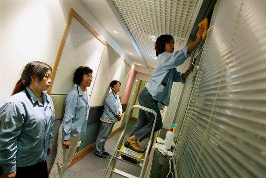 JOBLESS WOMEN LEARN TO CLEAN WINDOWS UNDER RETRAINING SCHEME IN HONGKONG.