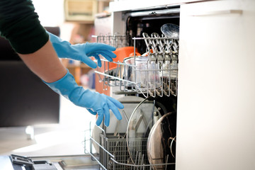 Woman opening the dishwasher in the kitchen , main focus on the gloves
