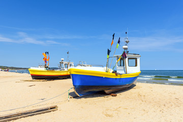 Colorful fishing boats on sandy Sopot beach in sunny day. Baltic sea, Pomerania.  Poland