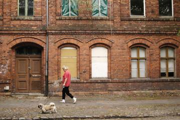 A WOMAN WALKS HER DOG IN A DERELICT WITTENBERGE STREET IN EASTERNGERMANY.