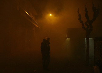 A policeman stands amongst thick smoke from tear gas and burning barricades outside the Athens Polytechnic