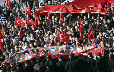 Mourners carry pictures of Turkish soldiers lost their lives in the clashes in south-eastern Turkey in Istanbul