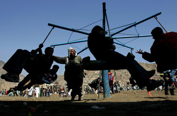 Afghan man pushes swing during Afghan New Year Day called Naw Ruz in Kabul