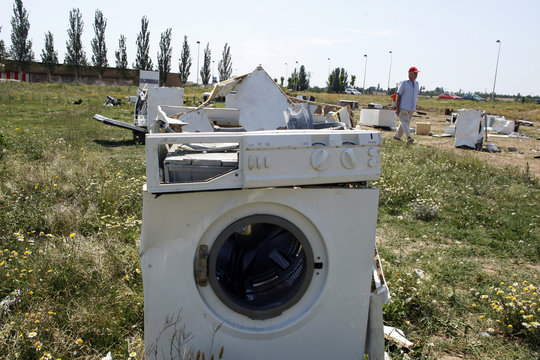 """A man walks past washing machines destroyed by with sledge-hammers following an anti-stress session or """"Destruction Therapy"""" in Castejon."""