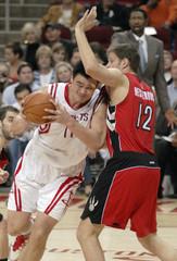 Houston Rockets' Yao of China drives into Toronto Raptors' Nesterovic of Slovenia in Houston