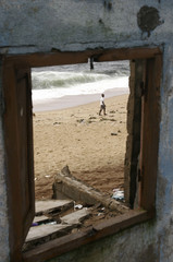 """A boy walks on the beach in front of the hotel """"les Tourelles"""" which was destroyed by sea erosion at Port-Bouet in Abidjan"""