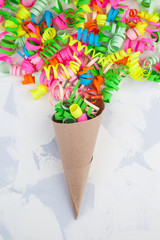 Close-up of colorful confetti and streamers with light background as template for birthday celebration or carnival