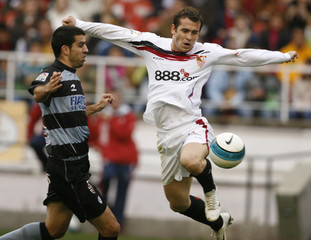 Sevilla's forward Alexander Kerzhakov of Russia jumps for the ball next to Real Sociedad's Juanito Gutierrez in Seville