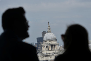 A couple are silhouetted as they look at St Paul's Cathedral in central London, Britain,