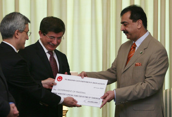 Pakistan's Prime Minister Yousaf Raza Gilani receives a placard of $10,000,000 cheque from Turkish Foreign Minister Ahmet Davutoglu in Islamabad