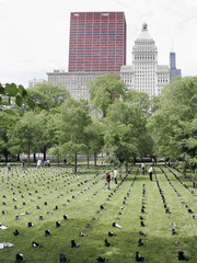 """People look at rows of boots which are part of """"Eyes Wide Open: An Exhibition on the Human Cost of the Iraq War""""  in Chicago"""