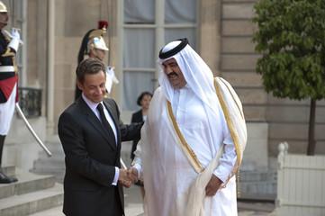 France's President Sarkozy welcomes Qatar's Emir Sheikh Hamad Bin Khalifa Al Thani as he arrives at the Elysee Palace in Paris