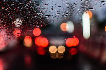 Abstact and bokeh background. Rain drops on car window in rainy season. raining car driving concept.
