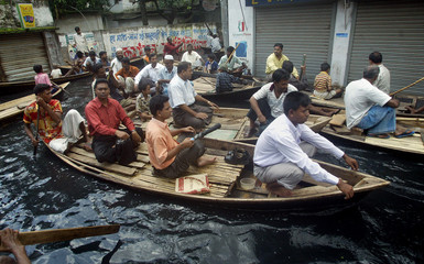 Bangladeshi flood victims move to their office by boats in Dhaka.