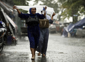 Women protect themselves with sheet of plastic as they walk through street in rain in Jakarta