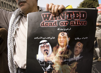 Iranian man holds a poster with images of pro-U.S. Middle Eastern leaders during a rally marking Qods (Jerusalem) Day in Tehran