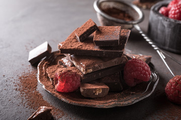 Broken chocolate pieces and raspberries with cocoa powder on metal plate on brown background with copy space. Dark photo.