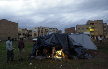 PEOPLE SET UP TENTS CLOSE TO DESTROYED BUILDINGS AFTER EARTHQUAKE IN MOROCCO.