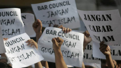 """A protester gestures in front of placards during a demonstration against """"Conversion to Islam"""" public forum in Kuala Lumpur"""