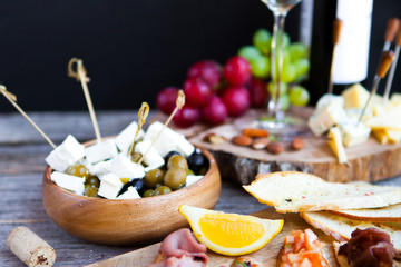 Glass with white wine, grape, cheese, over rustic wooden background. Wine snack set.